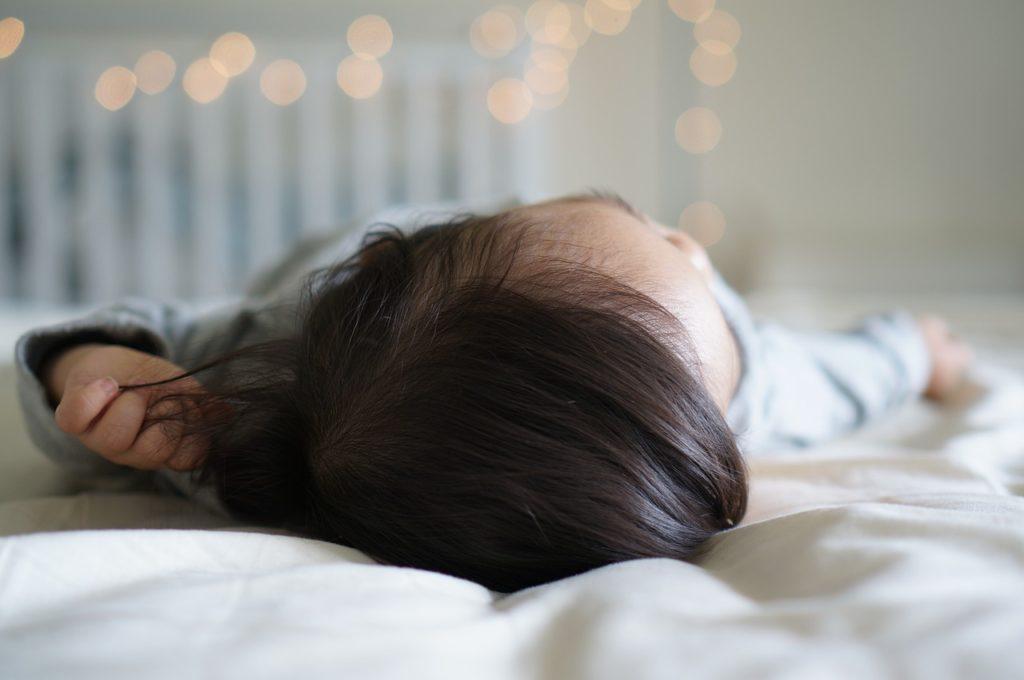 Kleinkind mit dunklen Haaren schläft im Bett